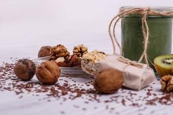 Gesunder grüner Smoothie mit Walnuss und Kiwi liegen auf dem Tisch
