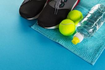 Gesundes Leben Sport Konzept. Sneakers mit Tennisbällen, Handtuch und Flasche Wasser auf hellem blauem Hintergrund. Text kopieren