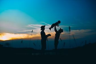 Glückliche Familie zusammen, Eltern mit ihrem kleinen Kind bei Sonnenuntergang. Vater, der Baby in die Luft hebt.