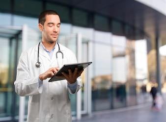 Glückliche junge Arzt mit einer Tablette