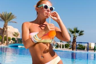 Glückliche junge Frau mit Cocktail