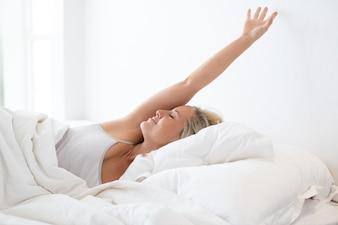 Glückliche junge Frau streckt sich im Bett nach dem Schlaf