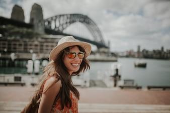Glückliche lächelnde Frau erforscht Sydney, mit Harbour Bridge im Hintergrund.
