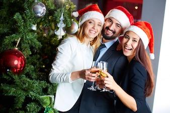 Glückliche Mitarbeiter mit Champagner feiern Weihnachten