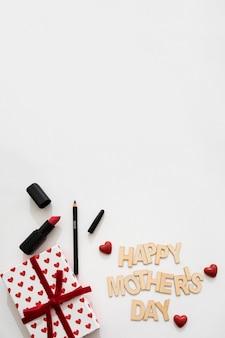 Glückliche Muttertagsschriftzug mit Lippenstift, Eyeliner und Geschenkkarton