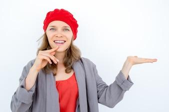 Glückliche nachdenkliche Frau zeigt gutes Produkt