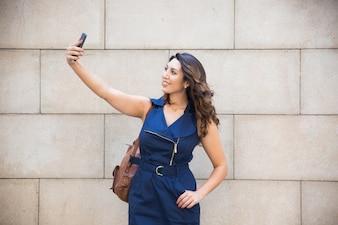 Glückliche schöne Dame posiert für Selbstporträt