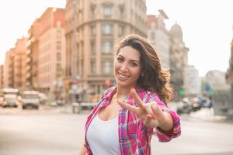 Glückliche schöne Frau zeigt Friedenszeichen