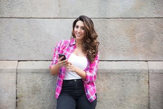Glückliche schöne junge Frau mit Smartphone im Freien