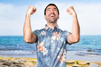 Glücklicher hübscher Mann mit Blumenhemd am Strand