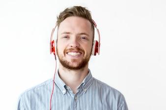 Glücklicher junger Mann hört Musik in Kopfhörer