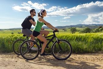 Glückliches junges Paar auf einem Fahrrad fahren auf dem Land