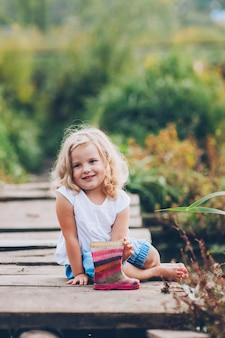 Glückliches kleines Mädchen auf einer Holzbrücke