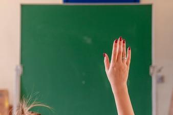 Glückliches Mädchen hob die Hände im Klassenzimmer