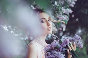 Gut gemachte junges Mädchen durch einige Blätter gesehen