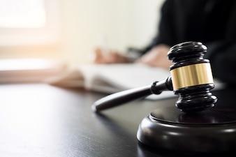 Hammer und Soundblock des Gerechtigkeitsgesetzes und des Rechtsanwalts, die an hölzernem Schreibtischhintergrund arbeiten.
