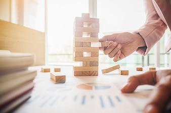 Hand der Geschäftsmannplanung, des Risikos und der Strategie im Geschäft. Glücksspiel des Geschäftsmannes, das Holzklotz auf einem Turm setzt.