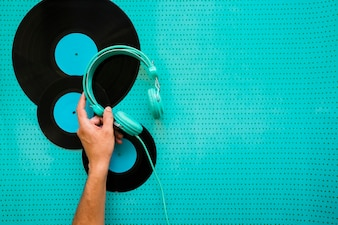 Hand, die Kopfhörer auf Vinyl setzt