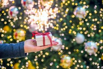 Hand hält ein Geschenk auf einem glänzenden Hintergrund