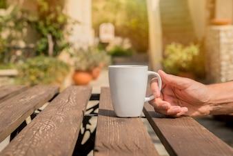 Hand hält eine Kaffeetasse. Man trinkt Morgen Kaffee mit einem grünen Hintergrund draußen. Mann Hände halten Tasse Kaffee im Café im Sommer Sommer