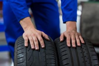 Hände der Mechaniker berührend Reifen