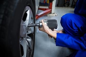 Hände der weiblichen Mechaniker, der ein Auto-Rad mit Druckluftschrauber Befestigung