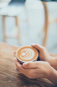 Hände, die eine Tasse Kaffee
