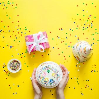 Hände mit Kuchen und Konfetti