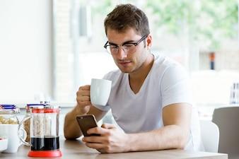 Handsome junge Mann mit seinem Handy beim genießen das Frühstück in der Küche.