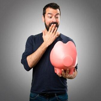 Handsome Mann mit Bart hält ein Sparschwein auf grauem Hintergrund
