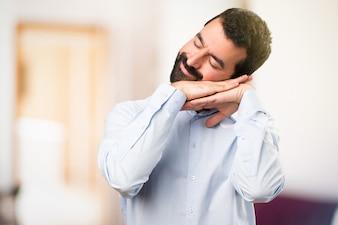 Handsome Mann mit Bart machen Schlaf Geste auf unfocused Hintergrund