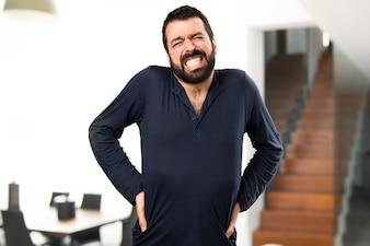 Handsome Mann mit Bart mit Rückenschmerzen im Haus