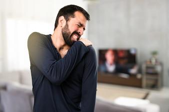 Handsome Mann mit Bart mit Schulter Schmerzen im Haus