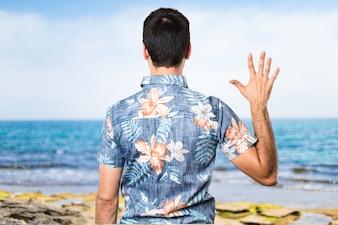 Handsome Mann mit Blumen-Shirt zählen fünf am Strand