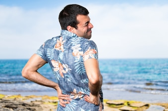 Handsome Mann mit Blumenhemd mit Rückenschmerzen am Strand