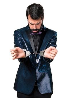 Handsome Mann mit Paillettenjacke mit Handschellen