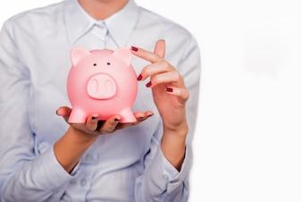 Happy Businesswoman holding Sparschwein vor weißem Hintergrund