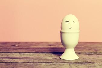 Happy Egg auf Holztisch, Bright Pink Pastell Hintergrund. Ostern oder glückliches Konzept. Weinlese Toning.