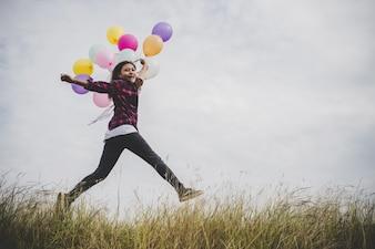 Happy Hipster Mädchen springen mit bunten Spielzeug Ballons im Freien. Junge Frau, die Spaß im grünen Feld gegen blauen Himmel hat. Frauen Freiheit Lebensstil Konzept.
