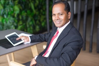 Happy Indian Business Man mit Tablet im Cafe