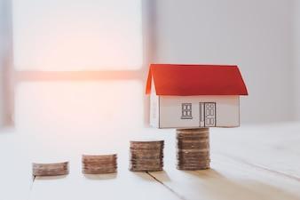 Haus aus dem Papier und Geld auf Holzuntergrund