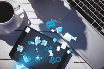 Helle blaue Symbole neben einer Tasse Kaffee und Laptop