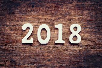 Hölzerne Zahlen, die die Nummer 2018 bilden, Für das neue Jahr 2018 auf einem rustikalen hölzernen Hintergrund.