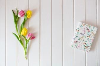 Hölzerner Hintergrund mit farbigen Tulpen und Buch