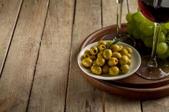 Holztablett mit Oliven, Trauben und Weingläsern