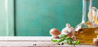 Holztisch mit Öl und Pilzen