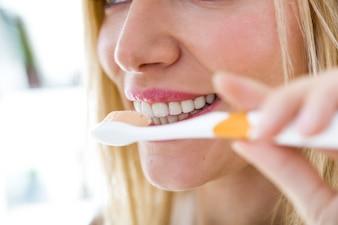 Hübsche junge blonde Frau Reinigung ihre Zähne.