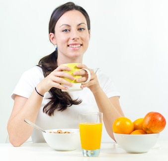 Hübsche junge Frau beim Frühstück zu Hause