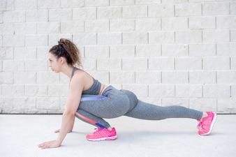 Hübsche sportliche Frau, die Beine nahe Backsteinmauer ausdehnt