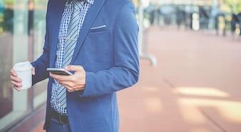 Hübscher junger Geschäftsmann, der sein Smartphone verwendet.